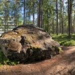 Kuva polusta metsässä, jossa ison kiven takana pilkottaa Paimion parantola.