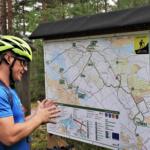 Mies katsoo Harjureitin karttaa pyöräilykypärä päässä.